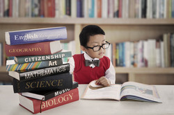 Portrait of little asian elementary school student studying by reading books of lessons