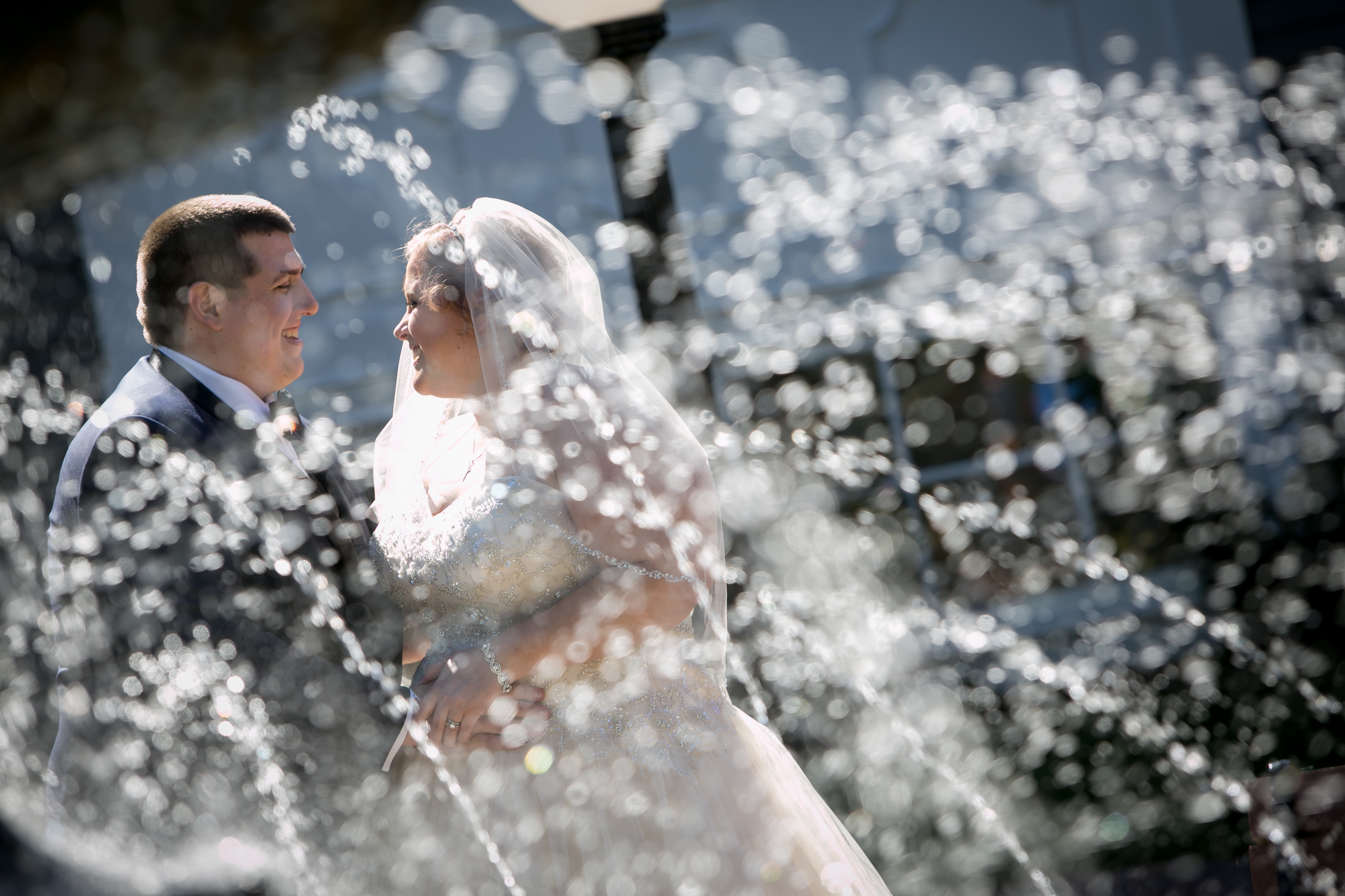 Bride and room Embrace Captured Through a Fountain
