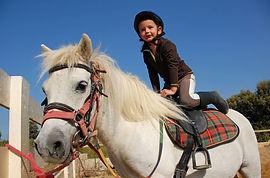 child-in-helmet-riding-horse.jpg