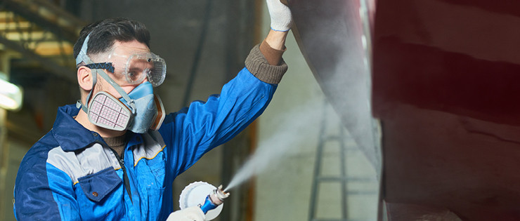 Worker wearing safety goggles and respirator