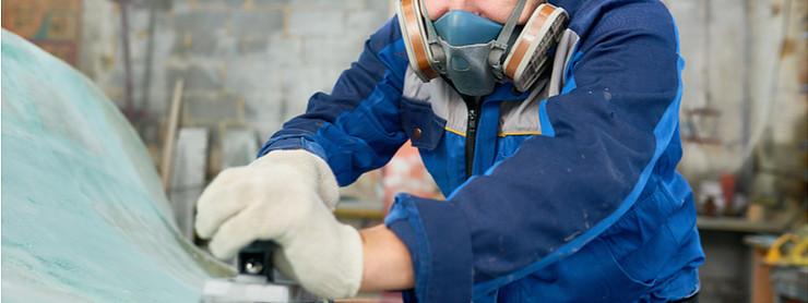 Man wearing respirator sanding