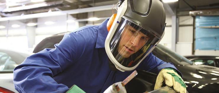 Worker wearing PAPR helmet