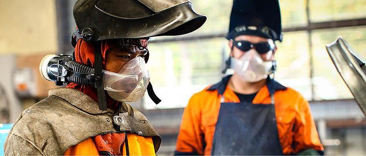 Welding workers wearing PAPR respirators