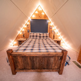 Turns out that next level is just a few lights, new bedsheets and some rustic homebuilt furniture.