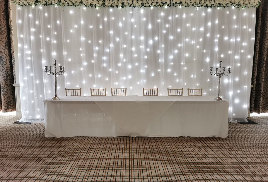 Flower Topped twinkling wedding backdrop