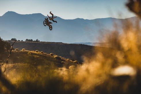 Motocross Photography: Professional freestyle motocross rider Adam Jones flies high against the setting sun