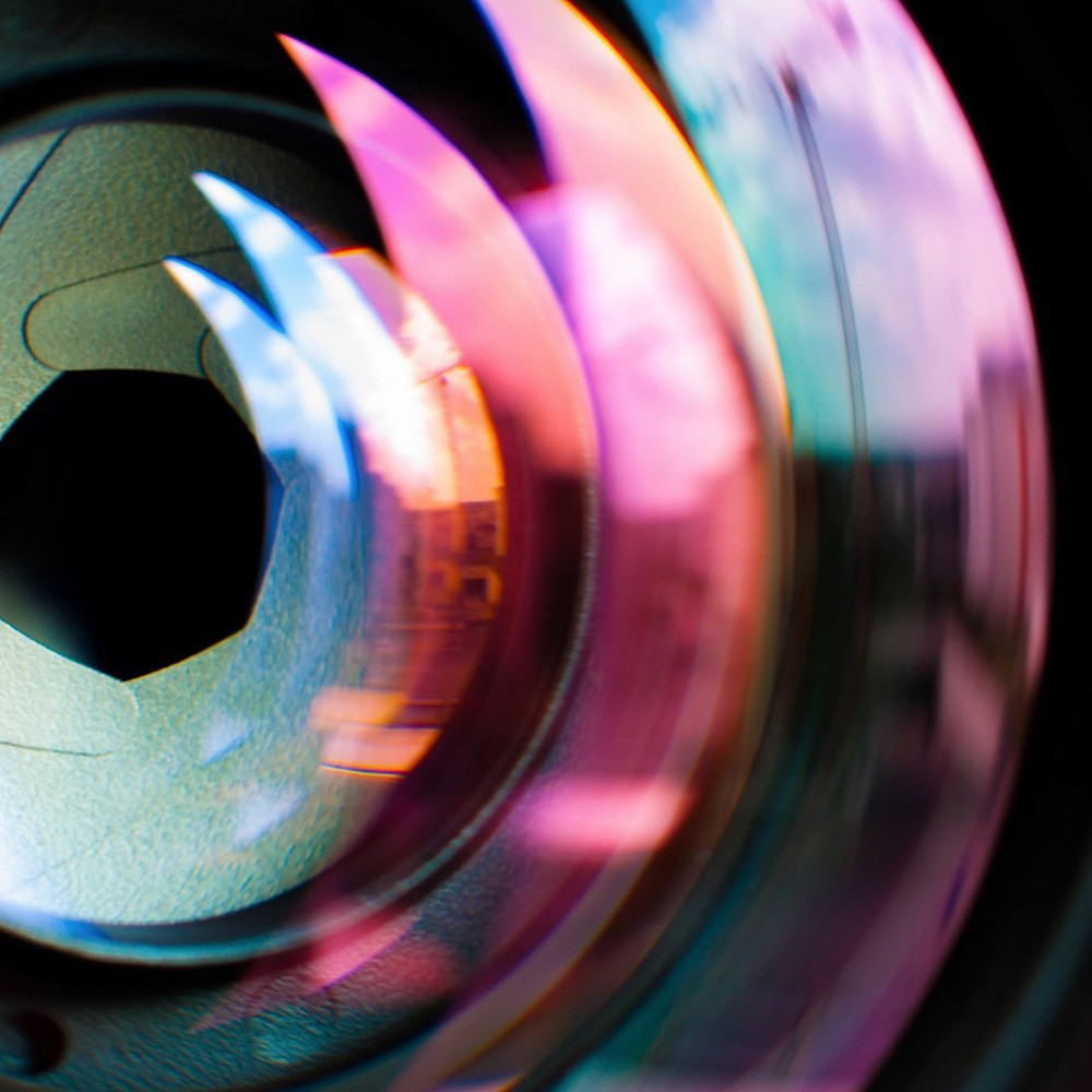 camera lens showing aperture and coloured refractions on glass
