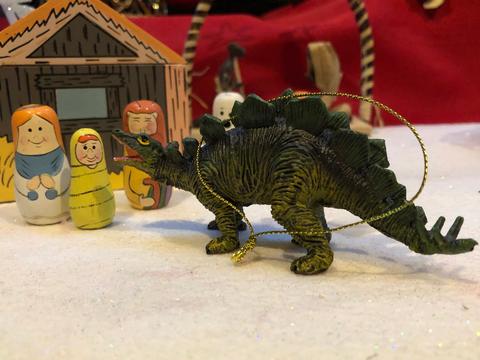 Stegosaur at nativity scene, worshiping baby Jesus