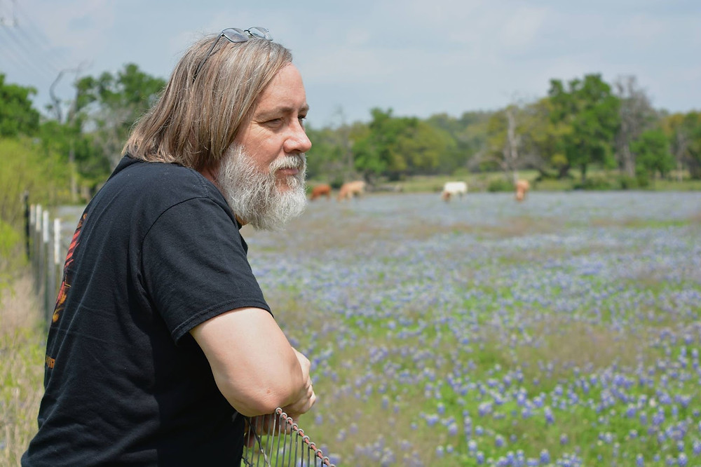 Author (Miles O'Neal) with bluebonnets and longhorns
