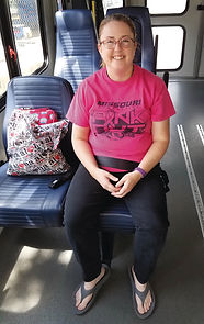 This is a picture of a smiling young girl riding the bus.
