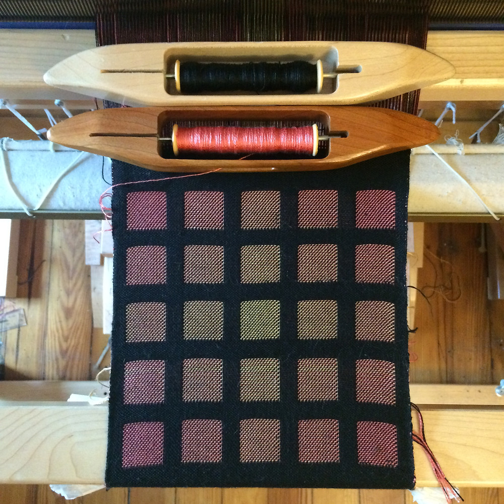 Double woven fabric on the loom in with a warm gradient block pattern on black.