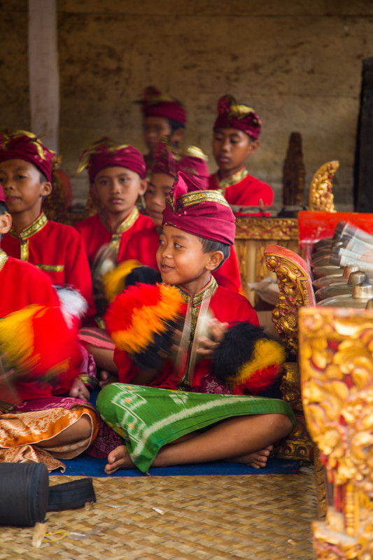 CHILD PLAYING MUSIC AT FULL MOON CEREMONY IN BALI INDONESIA