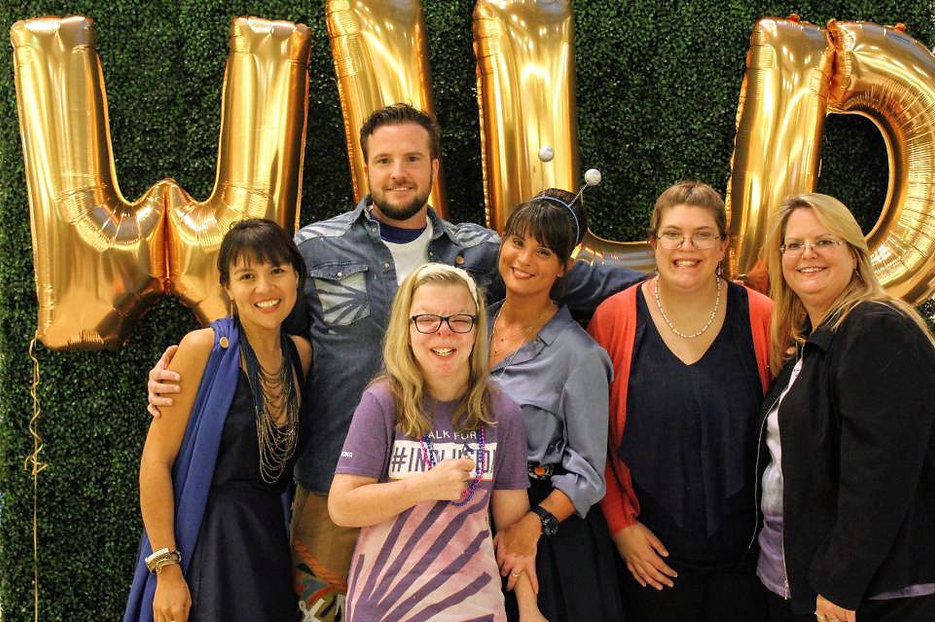 """group photo of 5 women, 2 with disabiltiies, and one man in front of backdrop with balloon letters spelling """"WILD"""""""
