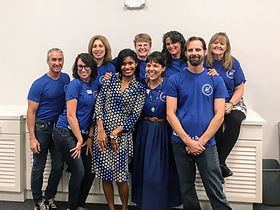 Group of 2 men and 7 women smiling while wearing blue t-shirts with logo for aZul For Better Living