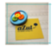 """circular, colorful button pin attached to square, yellow card with logo """"aZul For Better Living, Inc."""""""