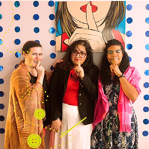 blurred image of 3 young women posed with 1 finger over their mouths, mimicking artwork hanging as backdrop