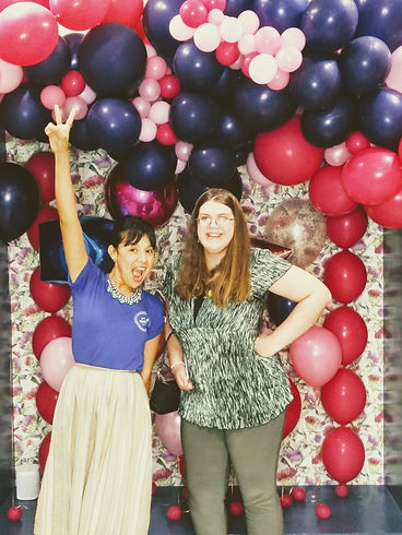 aZul Founder Sandra Raffaelli posing with peace sign in raised arm with Mariah in front of balloon backdrop