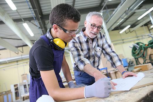 Carpenter with apprentice in training pe