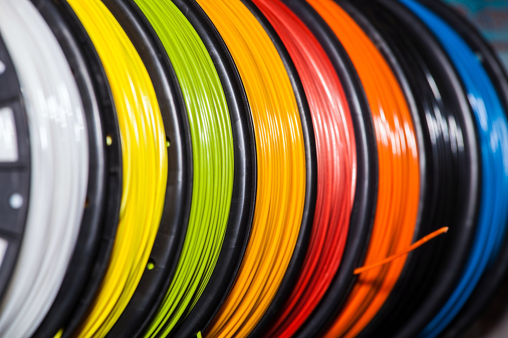 Multiple reels of 3D printer filament material, each in a different colour