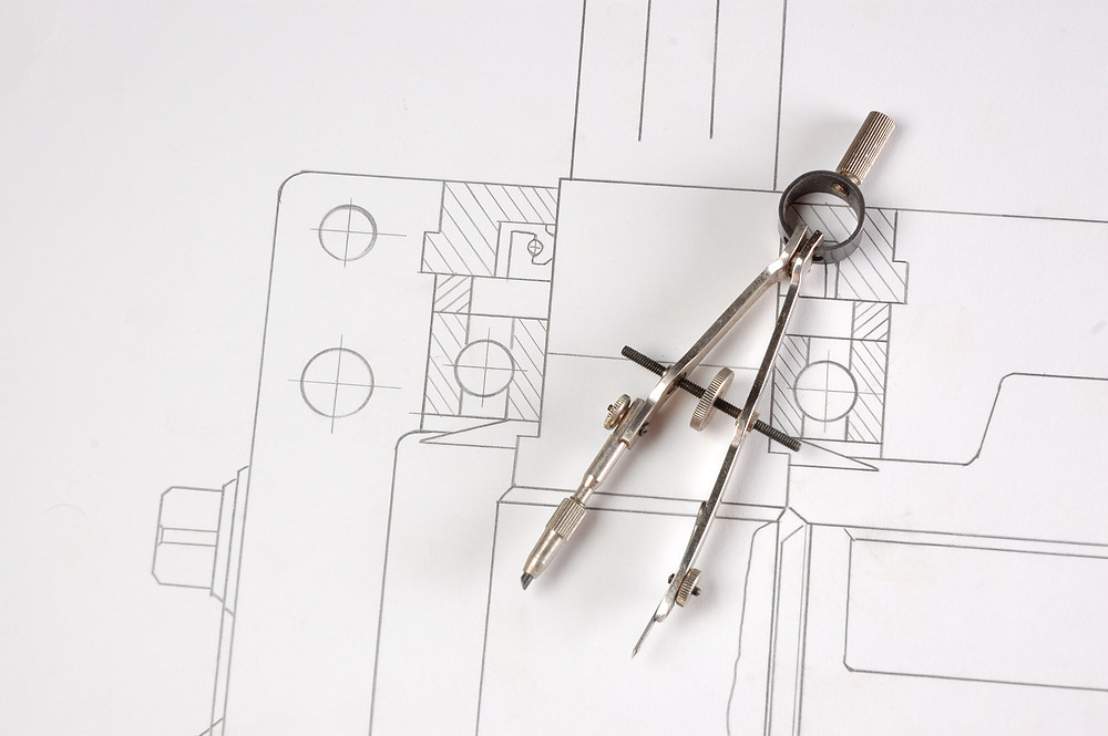 Design blueprint with a metal tool on top