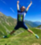 Annabelle Dougall jumping for joy atop Col du Glandon in the French Alps, with  Breakaway Cycle Tours
