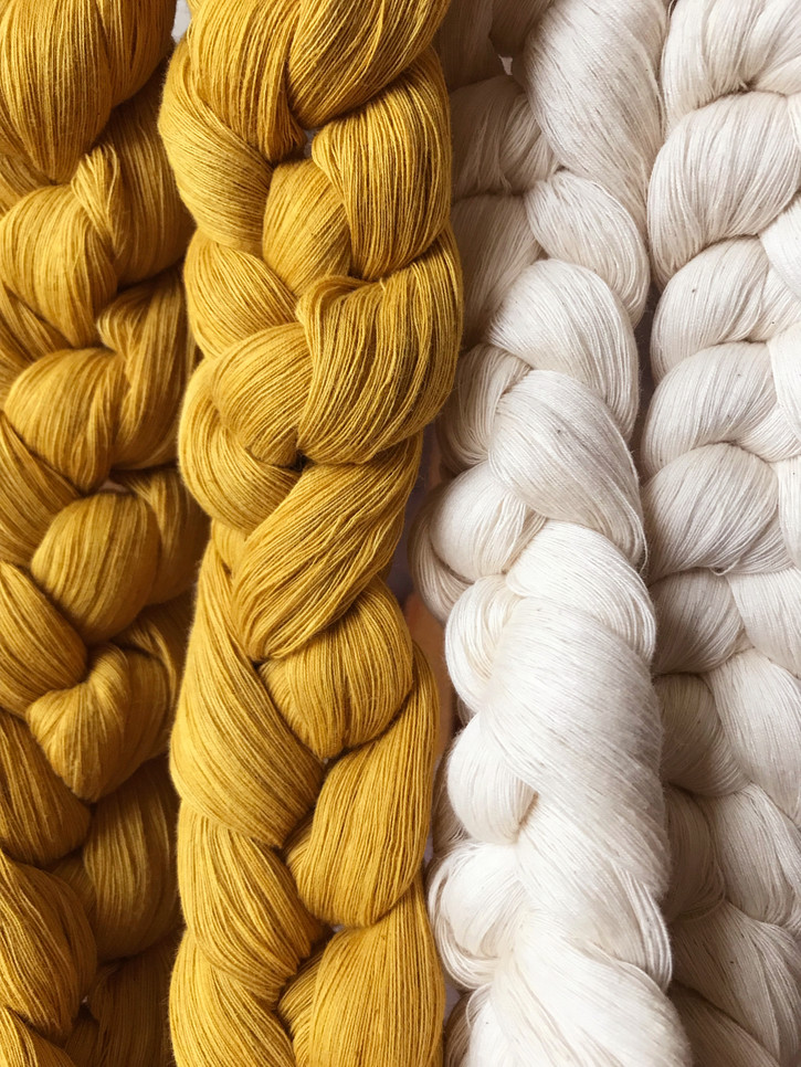 Organic cotton threads, undyed and dyed with osage and marigold, wound, chained