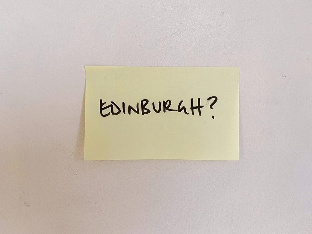 Post-it note with 'Edinburgh?' written on it, in black marker pen