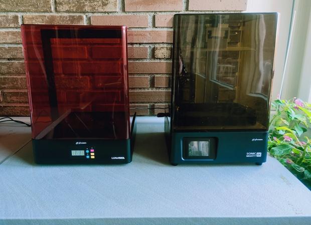 Impressora 3D Sonic Mighty 4K sobre bancada e do seu lado esquerdo o Forno Foto Phrozen Luna