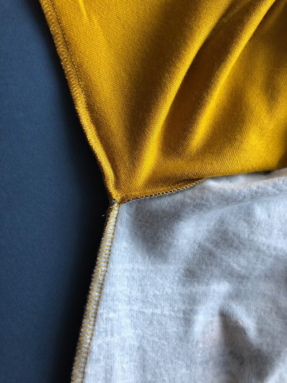 Gold overlocker thread on inside of baby romper