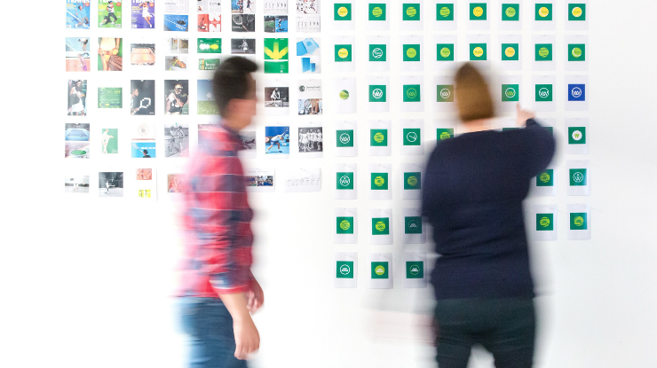 two people work on marketing plan on office wall
