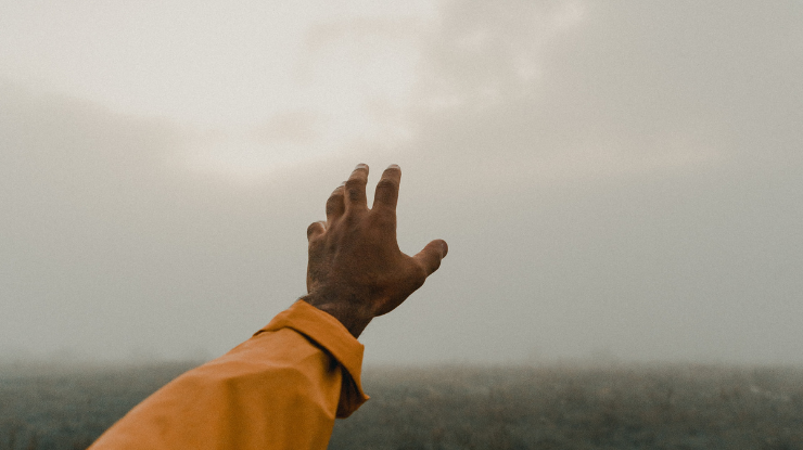 man in yellow jacket reaching out