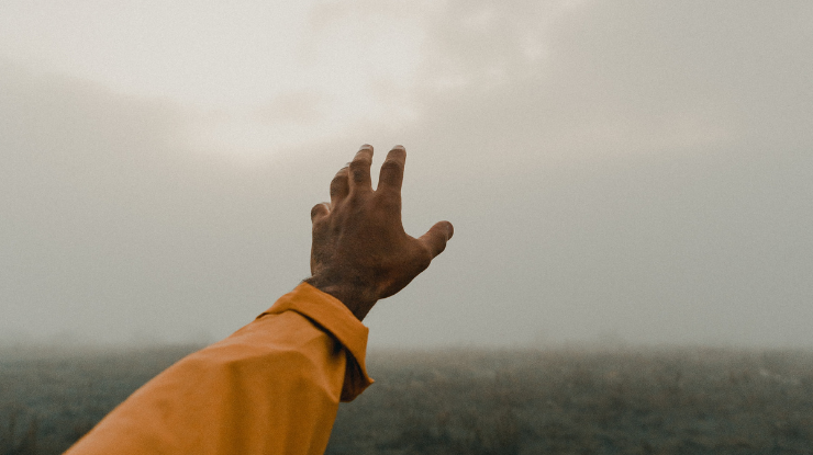 hand with orange sleeve reaching out to grey sky