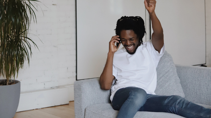 man sat on sofa in jeans and white celebrating phone call