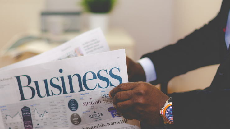 man in black business suit reading business newspaper