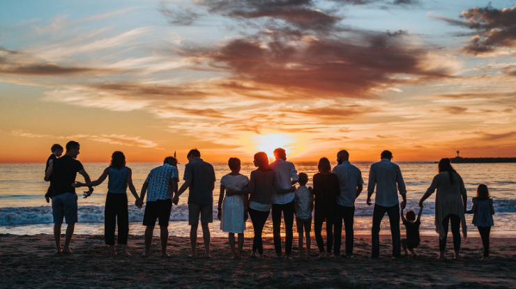 group of people gathered on the beach looking out at sunset