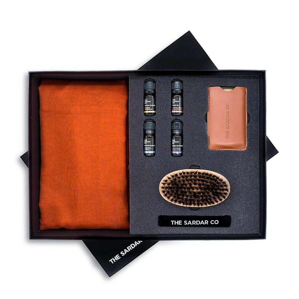 black box on white background containing three beard oils and beard comb