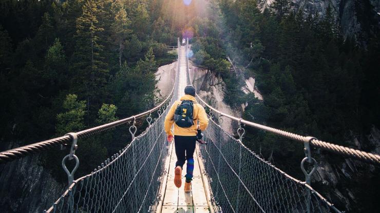 young explorer in yellow coat walking over rope bridge towards forrest
