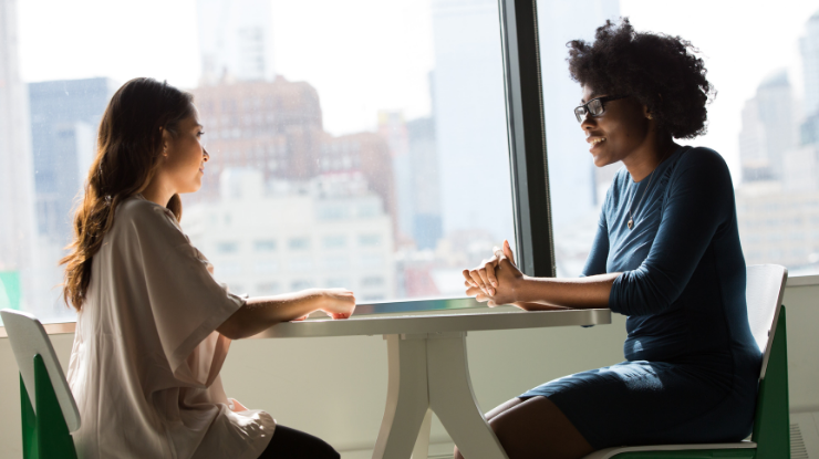 two women sat at a table having a meeting in front of a large window