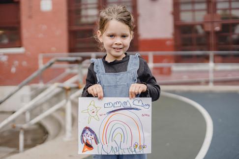Kind zeigt stolz seine Zeichnung
