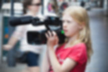A young girl uses a professional camera to shoot her film.