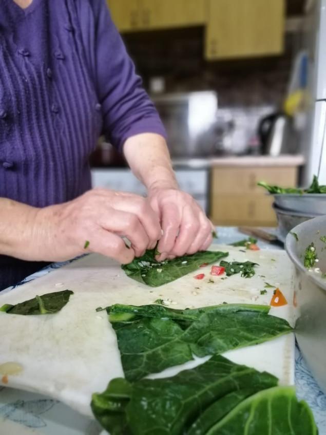 Grandma cooking stuffed cabbage leaves