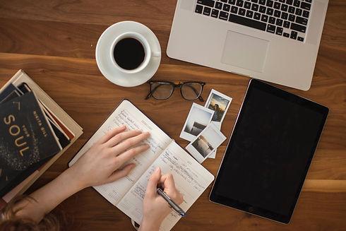 Skrivbord med dator och ipad och person som skriver anteckningar