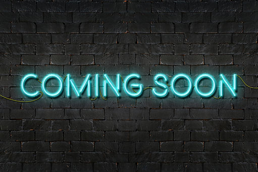 """COMING SOON"" neon sign shining on black"