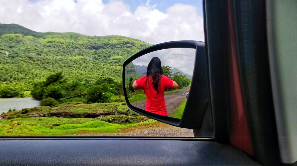 The reflection of the beautiful Tamhini Ghat in the side view mirror of the car