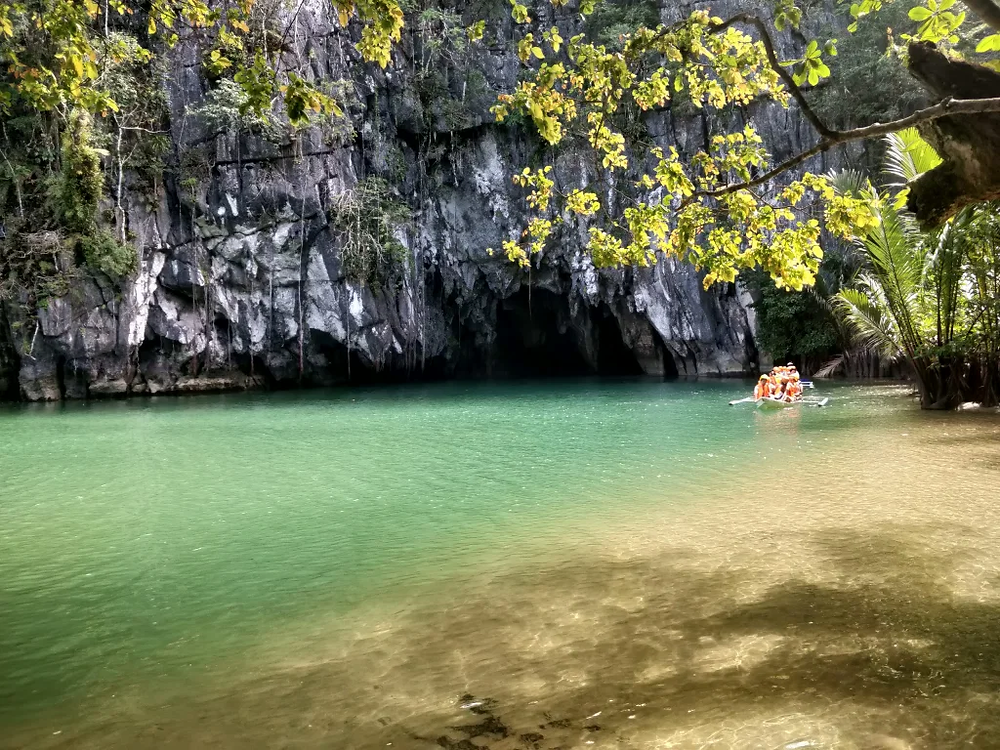 Dark and light green water leading to an underground cave
