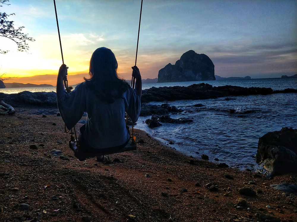Woman watching the sunset on a swing in a secluded beach