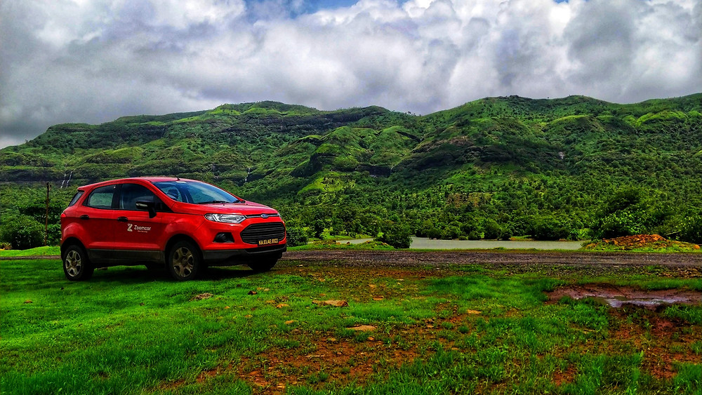 The car parked along the hills of a lush green Tamhini ghat