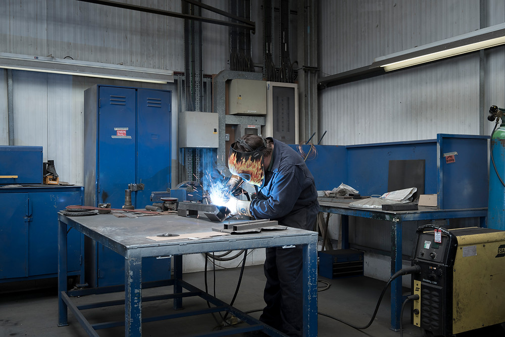 Metal worker skilfully welds plates together