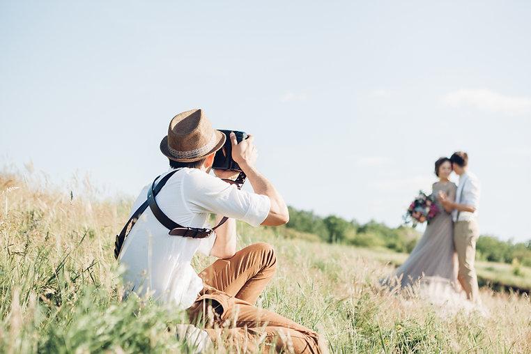 Photographe en pleine action de shooting en exterieur sur un mariage