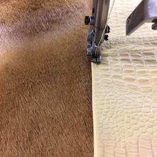 Finition avec une bordure surpiquée pour un tapis en peau de vache